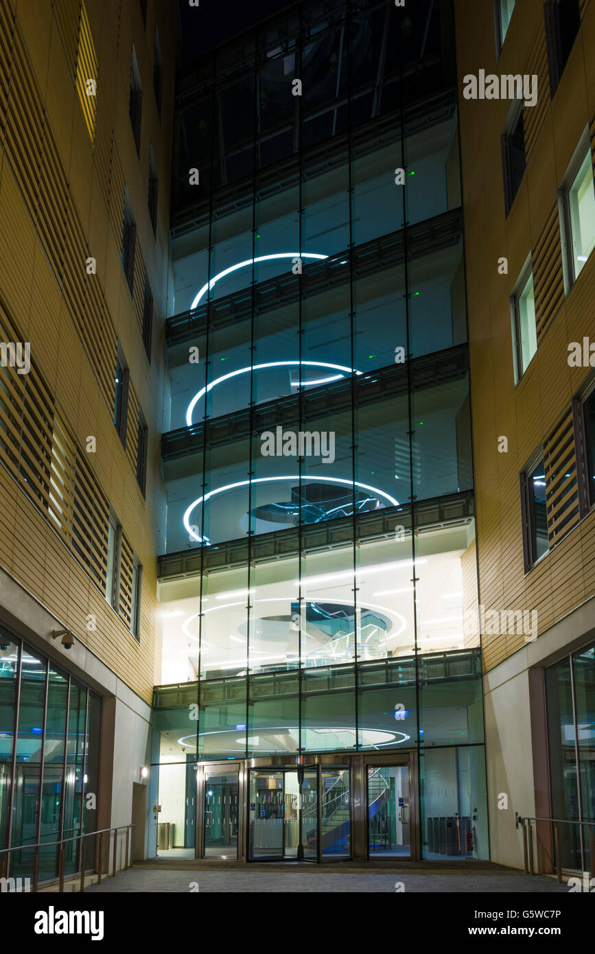 Glass fronted office block illuminated at night, Temple Quay, Bristol, England. - Stock Image