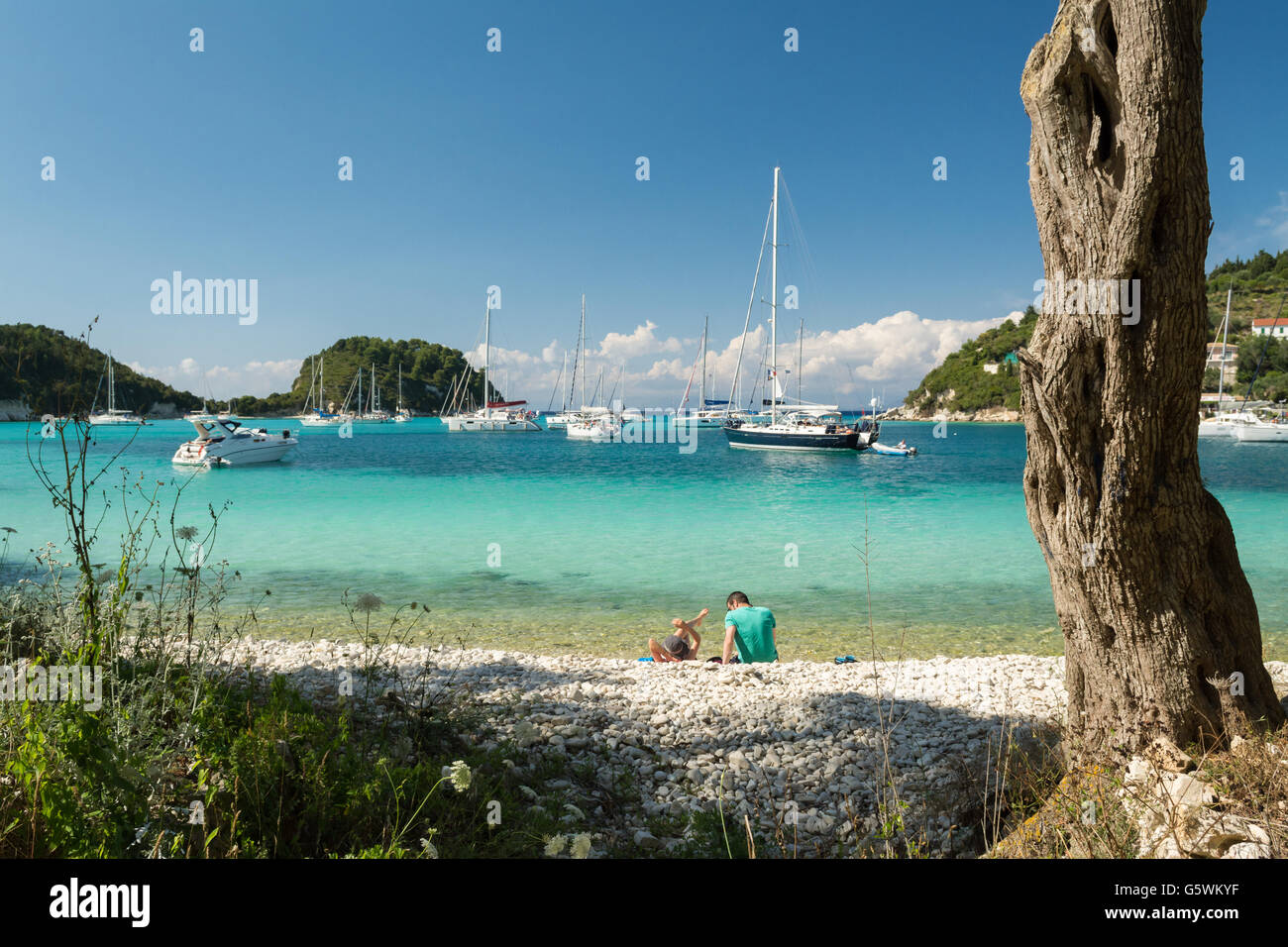 young couple relaxing on Harami Beach looking out at the turquoise waters of Lakka Bay, Lakka, Paxos, Greece - Stock Image