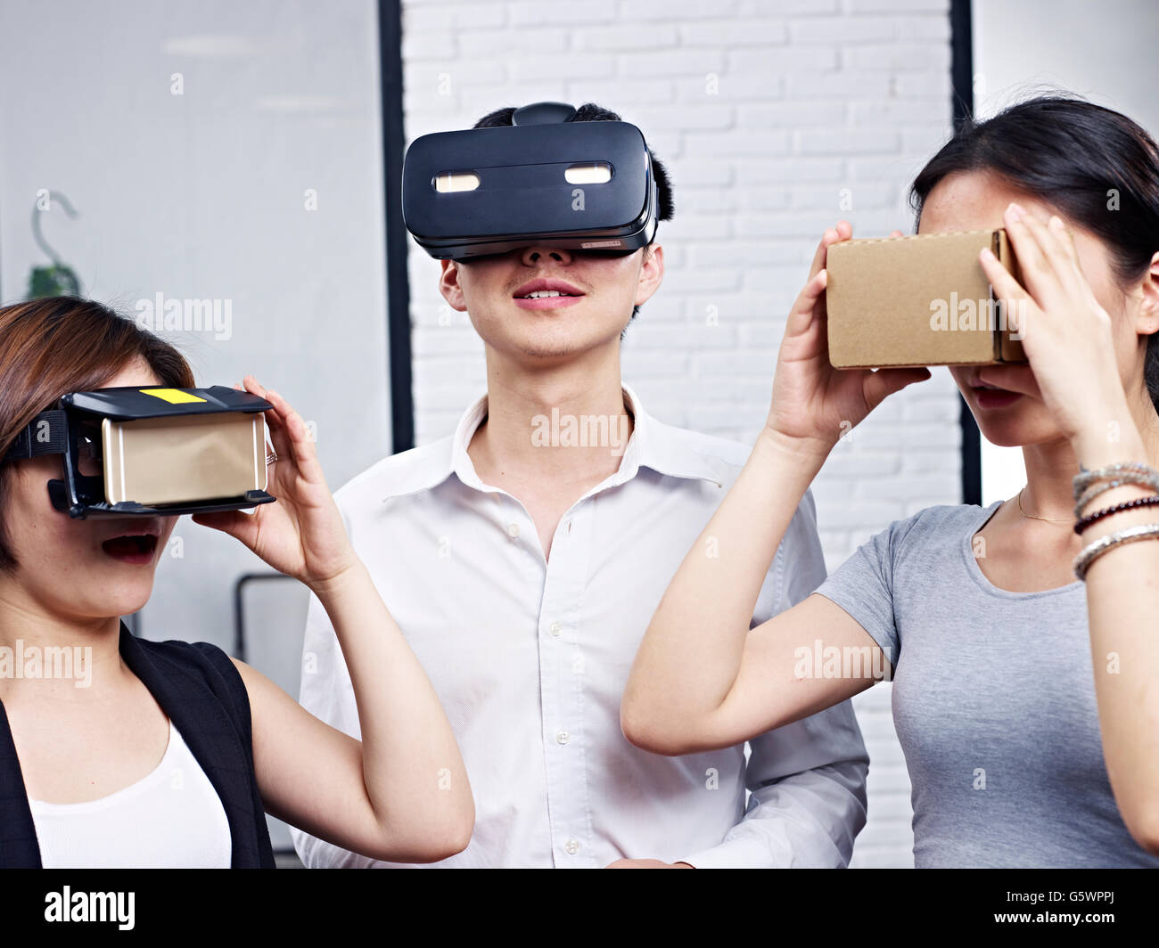 three young asian people wearing different types of virtual reality (VR) goggles. - Stock Image