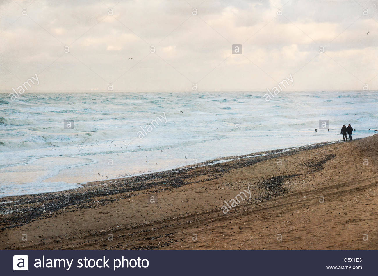 two persons walking on the beach - Stock Image