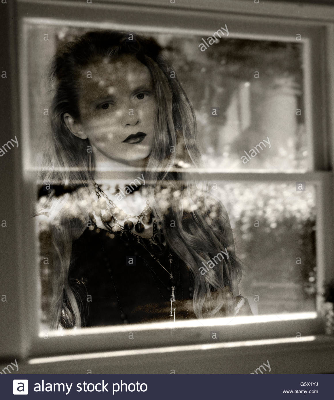 Young woman looking through window. Stock Photo