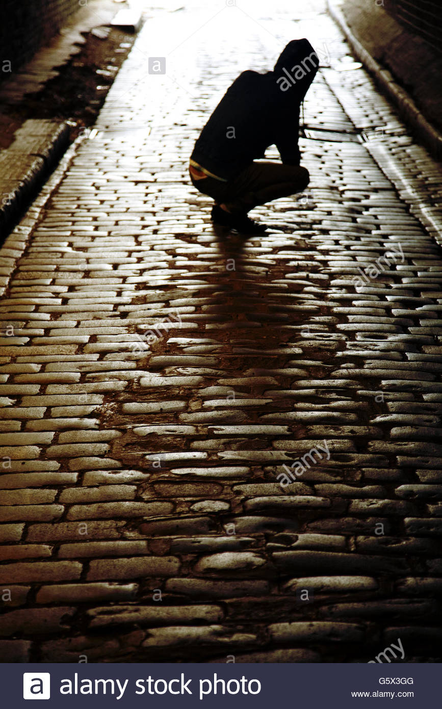 Man Crouched on Cobbled Alleyway - Stock Image