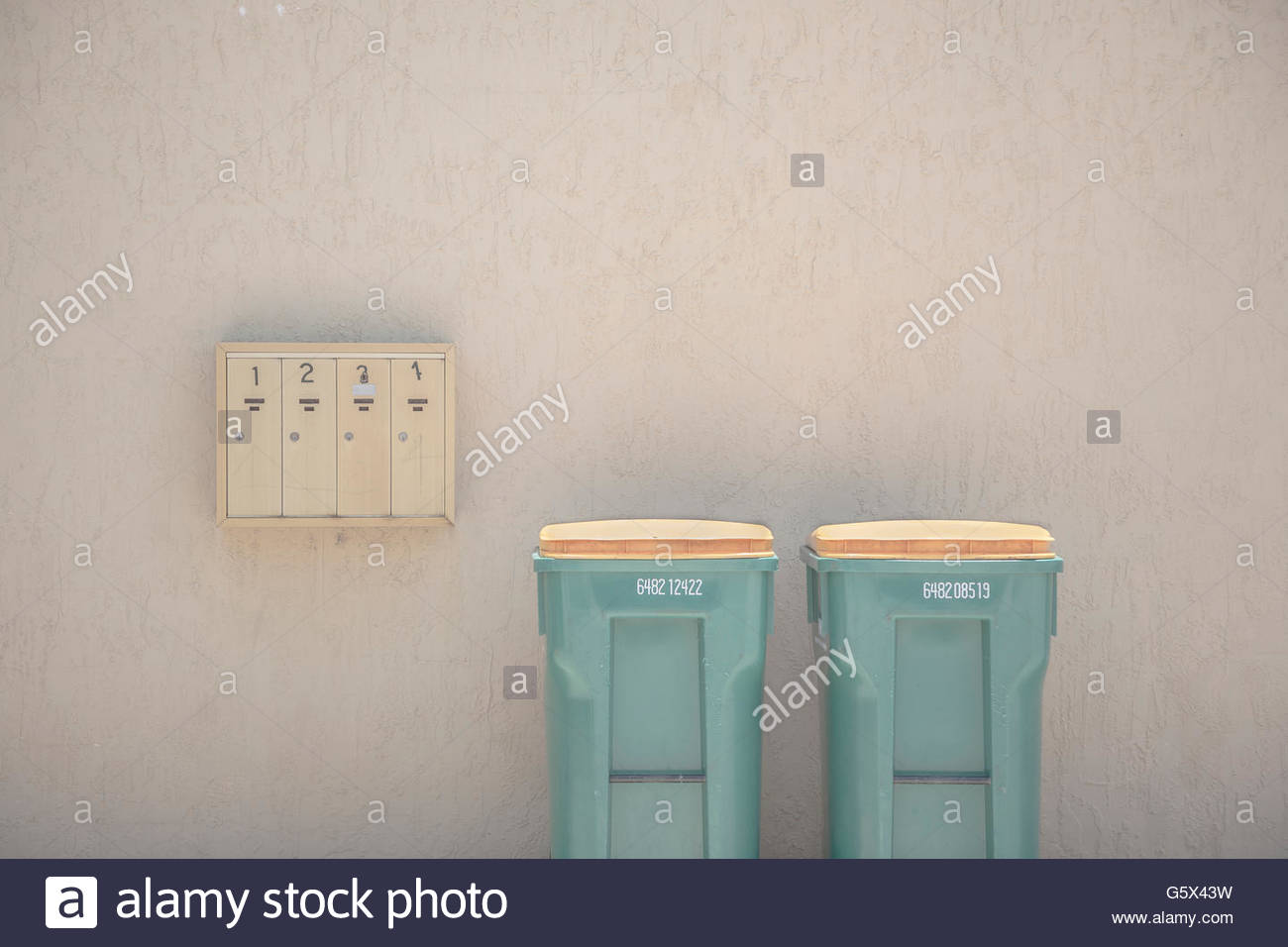 Mail boxes and trash cans in front of an apartment. - Stock Image
