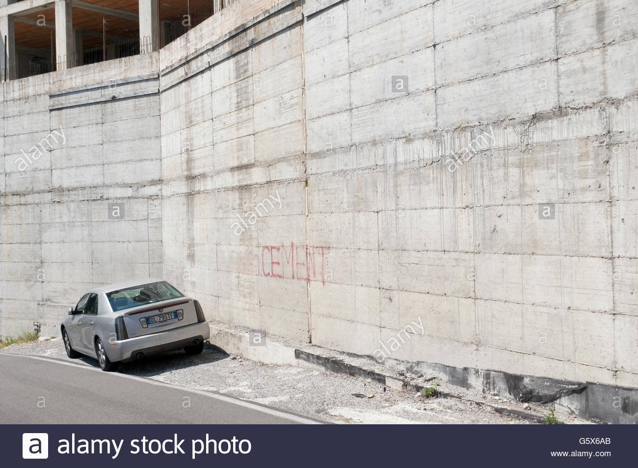 Parked car and armored concrete wall - Stock Image