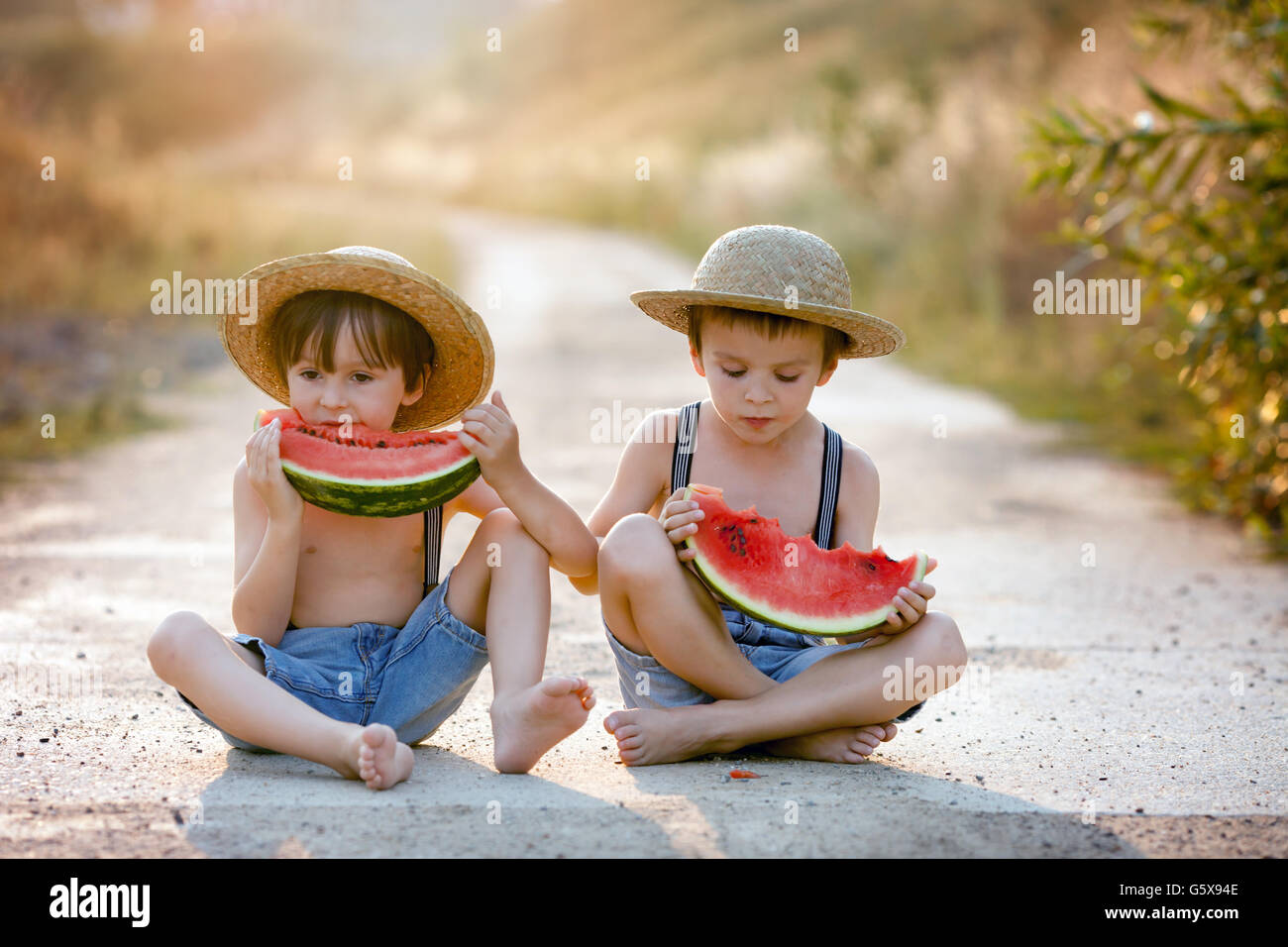 Two cute little boys, eating watermelon on a rural village path, summertime - Stock Image