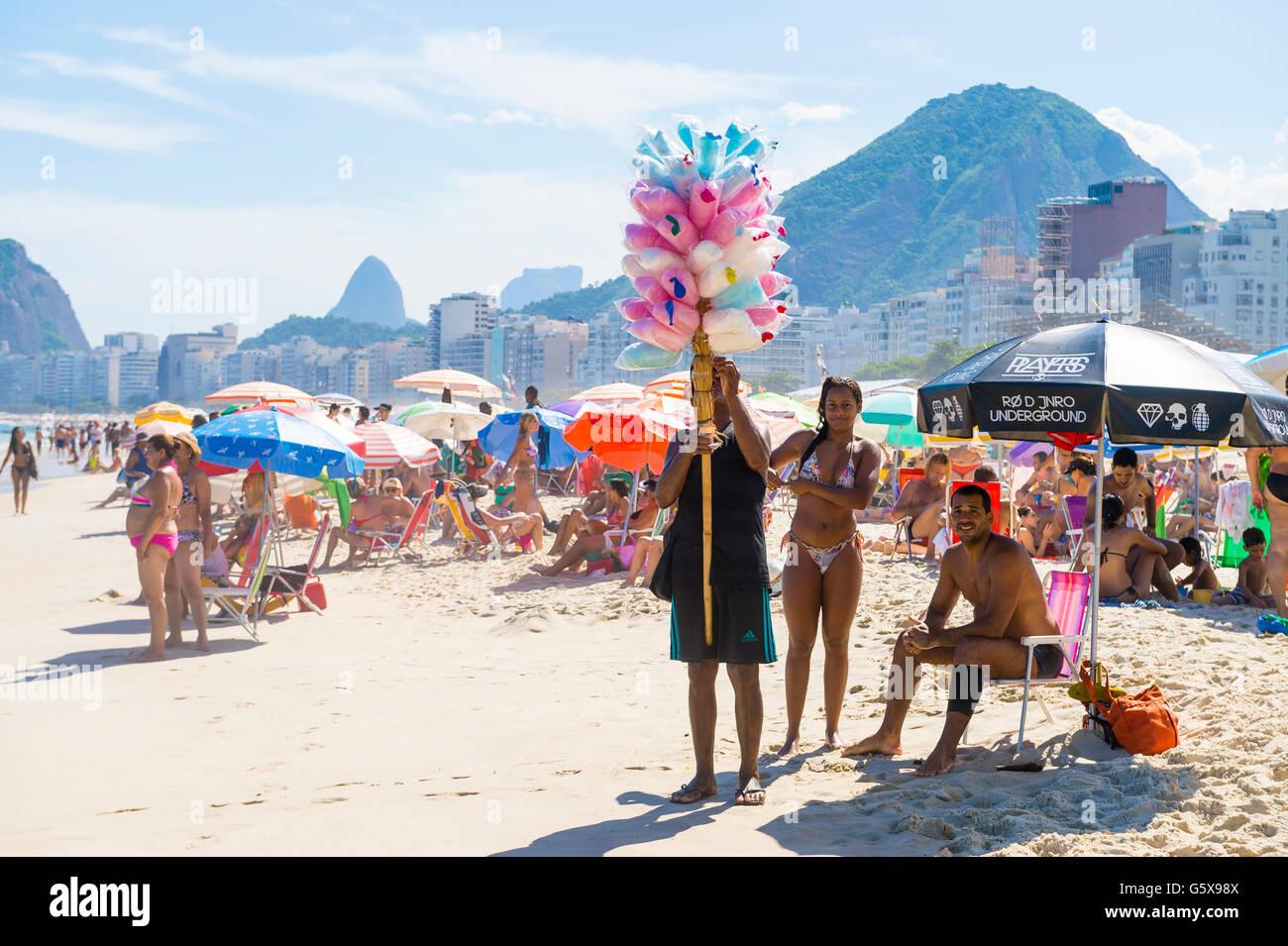 RIO DE JANEIRO - FEBRUARY 27, 2016: Brazilian beach vendor selling cotton candy floss approaches customers on Copacabana - Stock Image