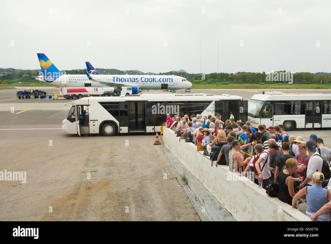 holidaymakers queuing to board bus to transfer to Thomas Cook plane at Corfu airport, Greece, Europe - Stock Image
