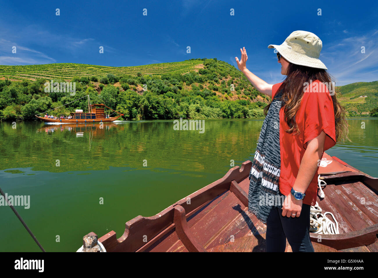 Portugal: Girl with hat in traditional Rabelo boat greeting other boat on river Douro Tour Stock Photo