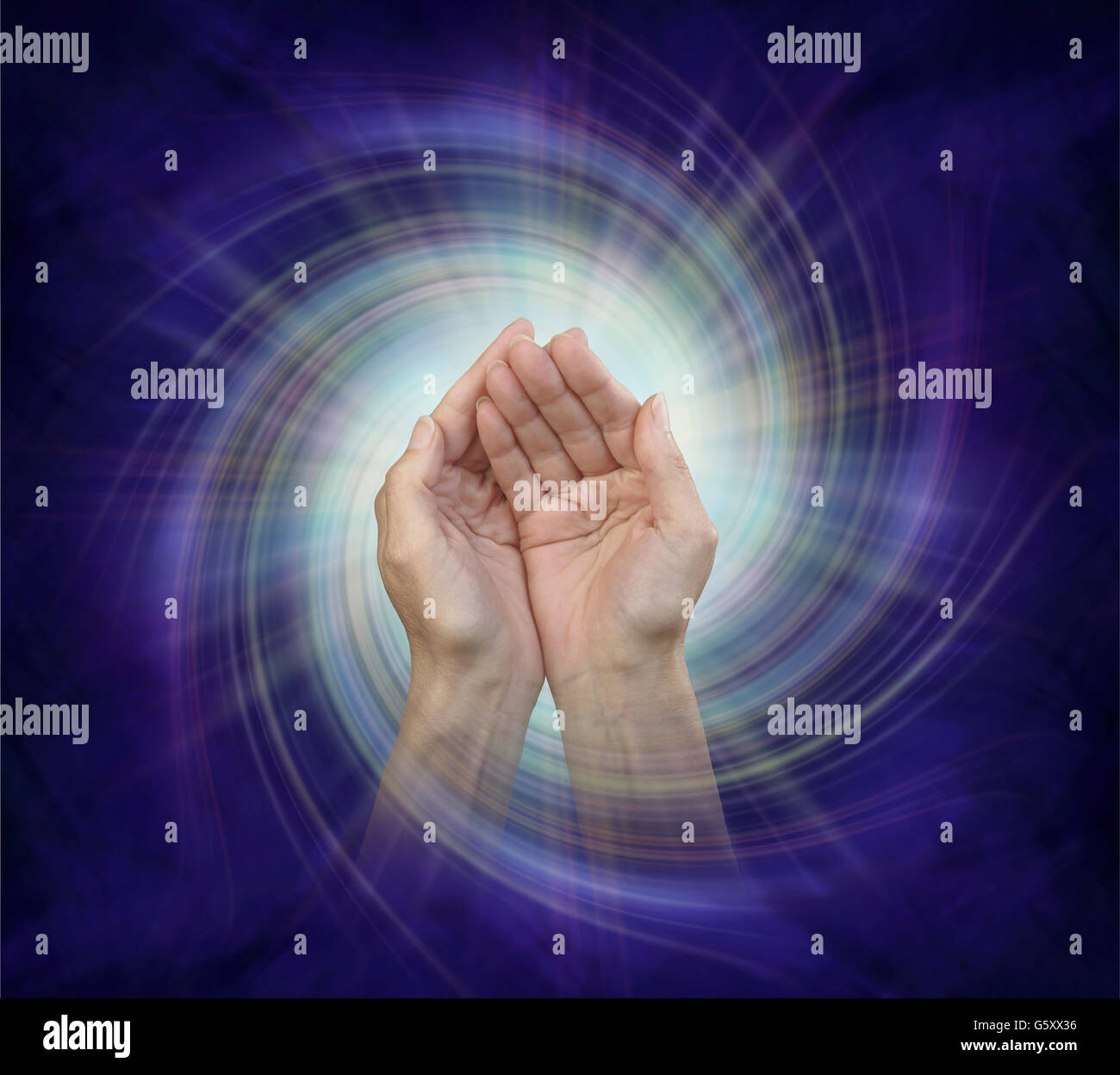 cupped hands with a fine multicolored light burst behind on a white vortex spiraling against a dark ultramarine - Stock Image