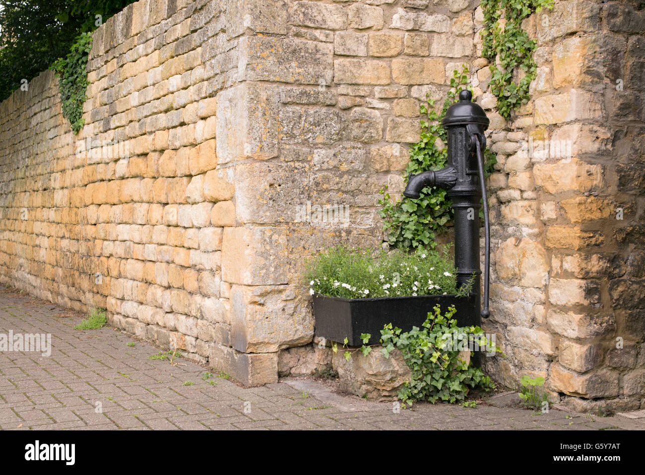 Old cast iron hand water pump and trough with flowers on the street in in Chipping Campden, Gloucestershire, England Stock Photo