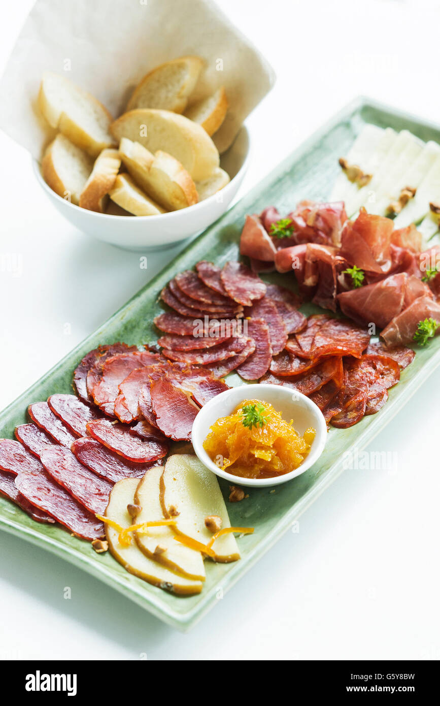 spanish serrano ham chorizo sausage smoked meats cheese tapas sharing platter set with bread - Stock Image