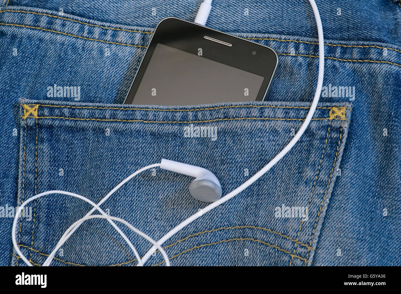 smartphone with earbuds in the back pocket - Stock Image
