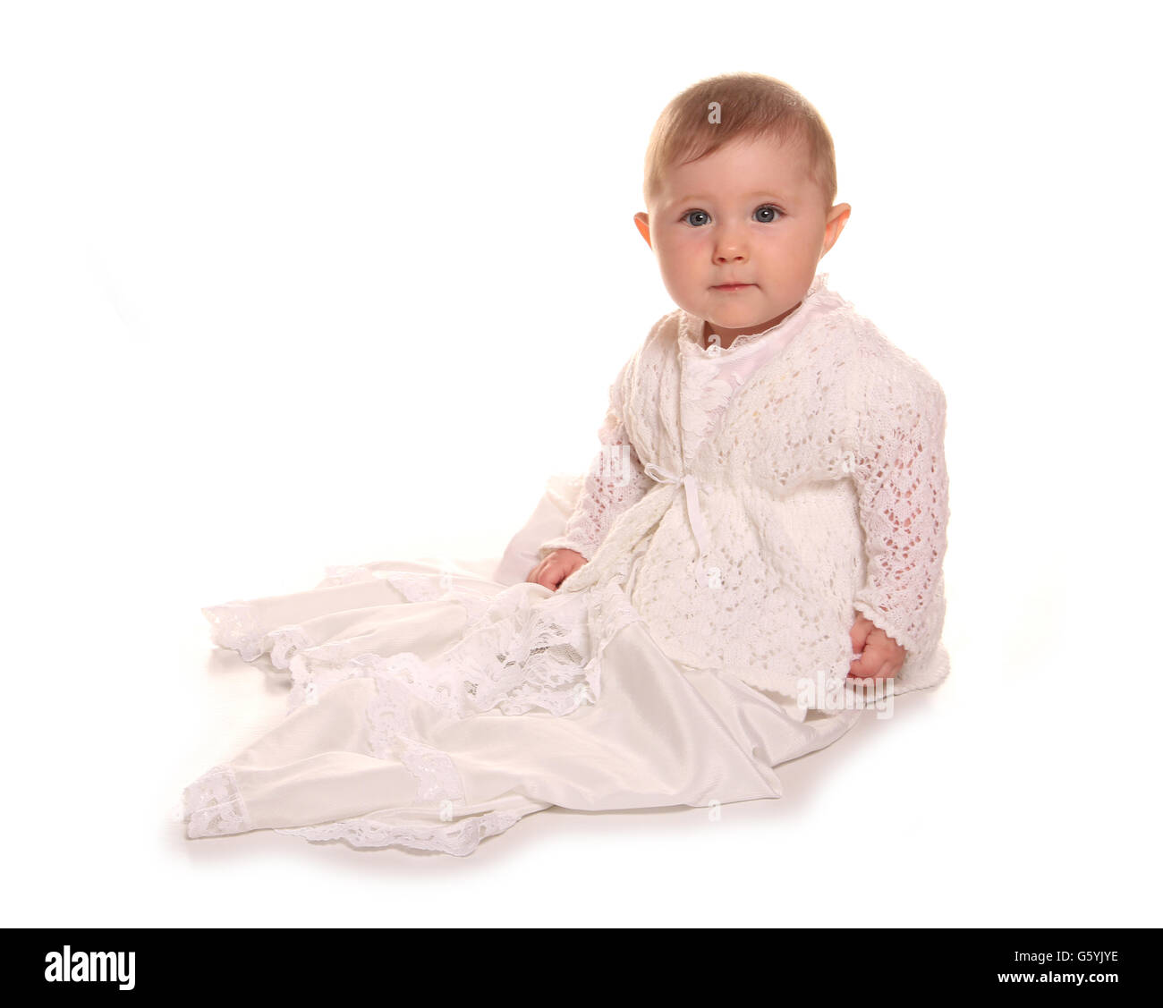 baby girl in a christening gown cutout - Stock Image