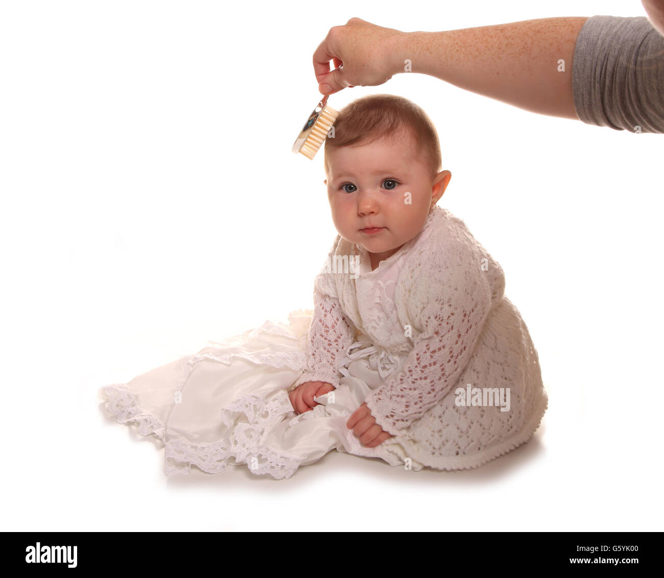 Mother combing babys girls hair before christening cutout - Stock Image