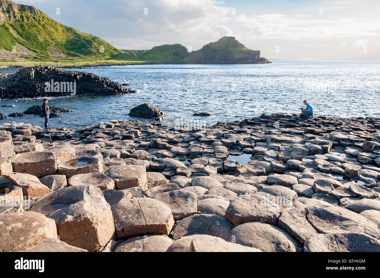 Tourists taking photos on Giants Causeway, unique geological hexagonal formations of volcanic basalt rocks in Northern Stock Photo