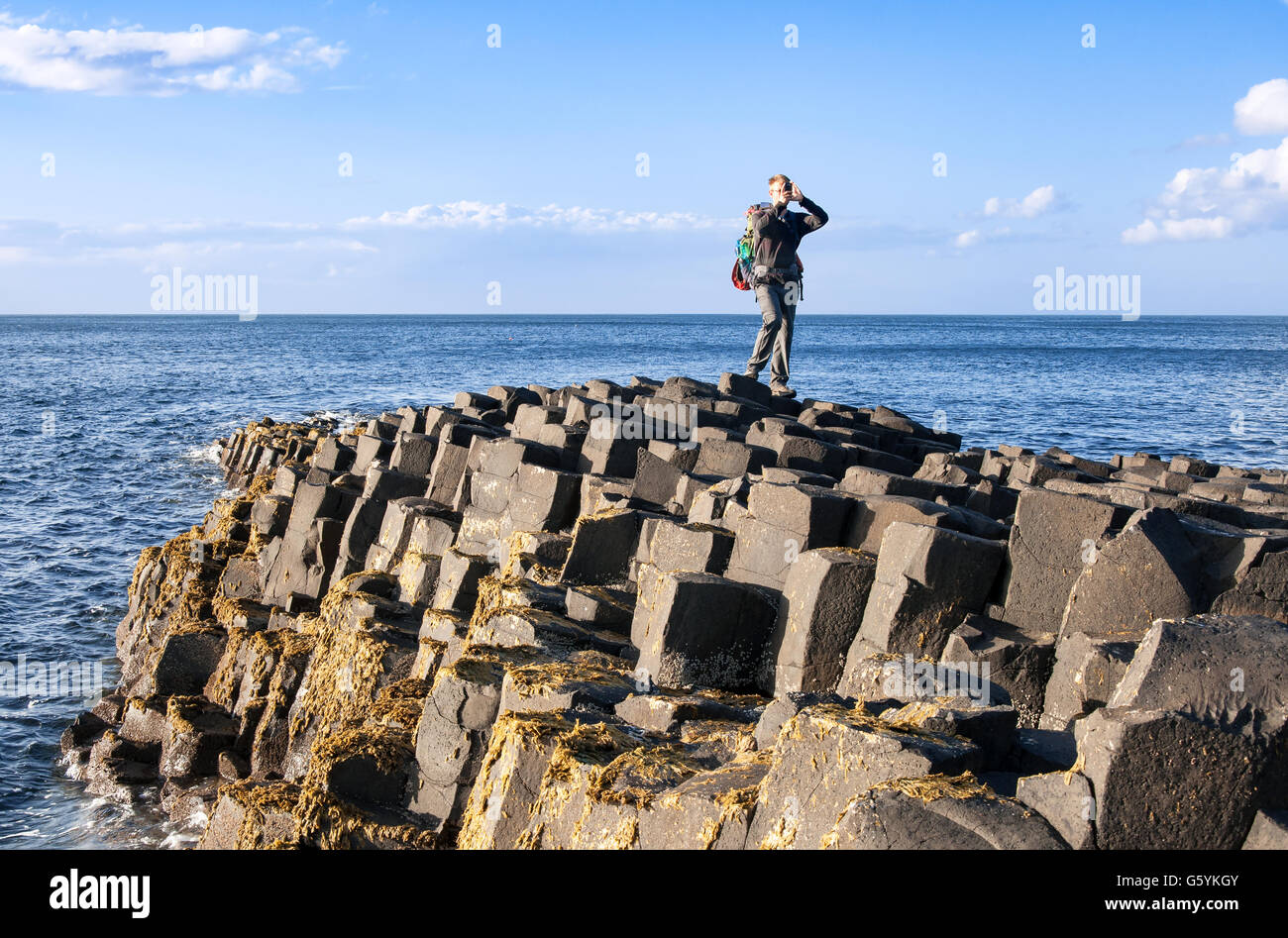 A tourist taking photos on Giants Causeway, unique geological hexagonal formations of volcanic basalt rocks in Northern - Stock Image