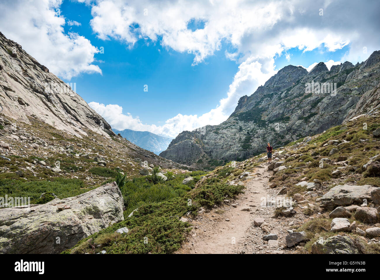 Young man hiking on a trail through the Golo Valley Nature Park of Corsica, Parc naturel régional de Corse, - Stock Image