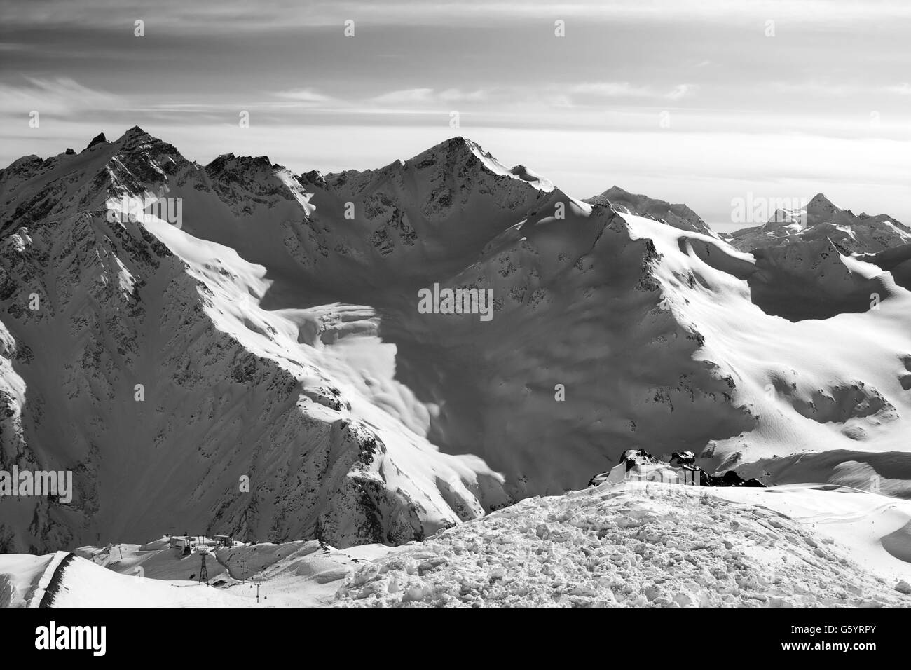 Black and white Snowy off-piste slopes at evening. Caucasus Mountains. View from ski slope of Mount Elbrus. - Stock Image