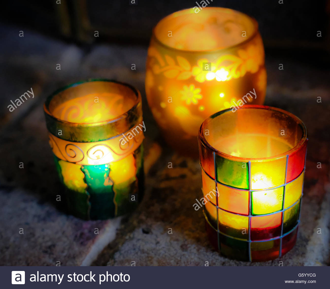 Festive, coloured glass jar lanterns as seen with lit tea lights in a fireplace setting. - Stock Image