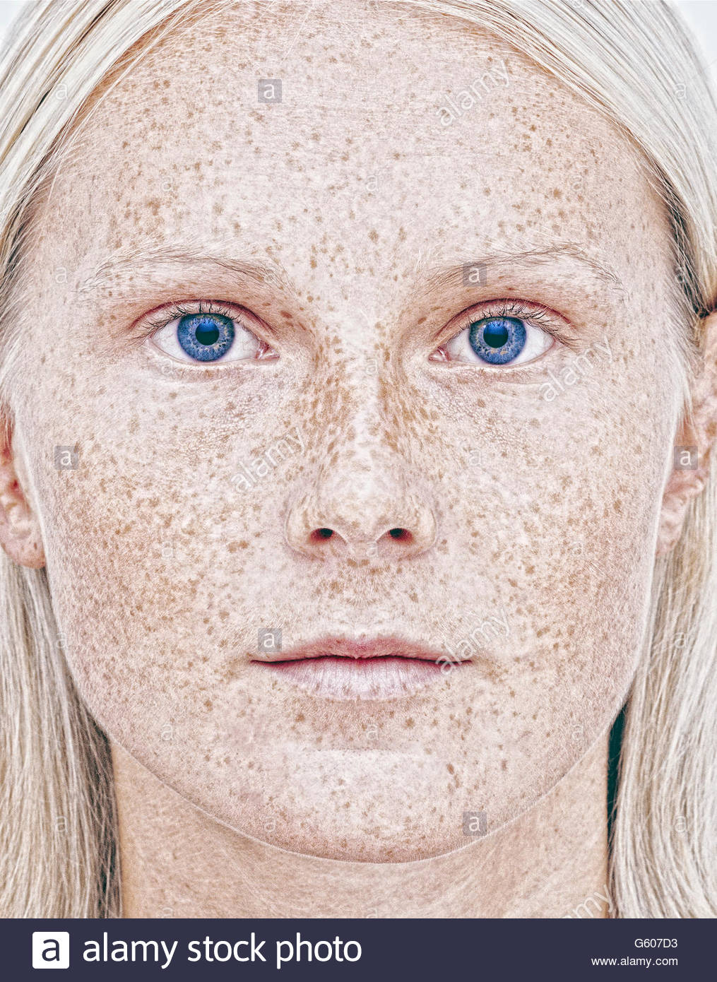 Portrait of young woman with freckled face - Stock Image