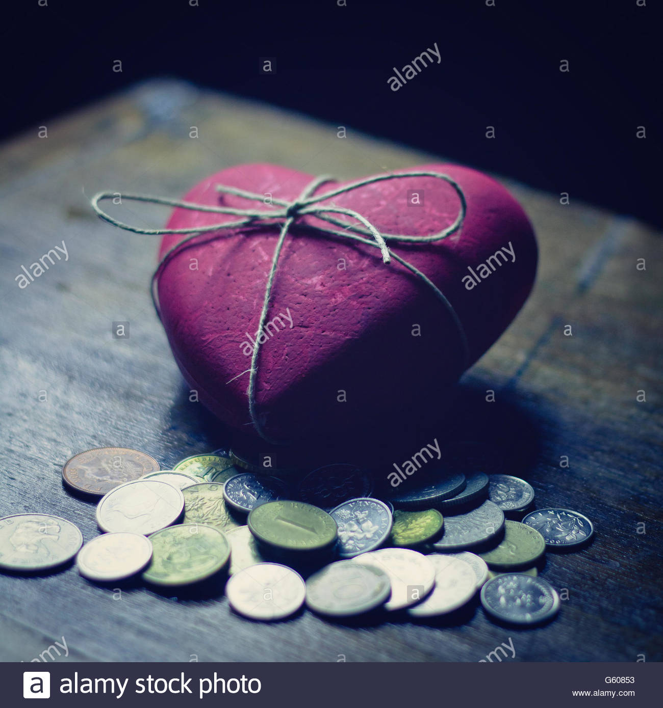Red heart with coins Stock Photo