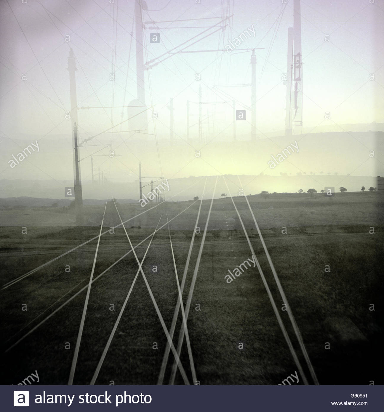 View from a train of horizon and train tracks overlapping in sunset Stock Photo