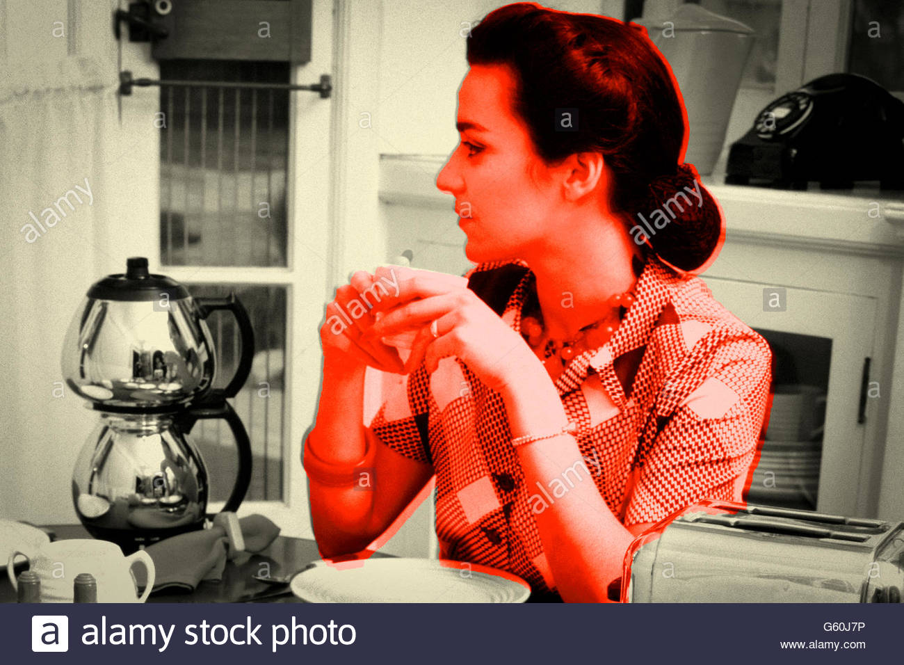 Retro Styled woman at breakfast holding coffee mug. - Stock Image