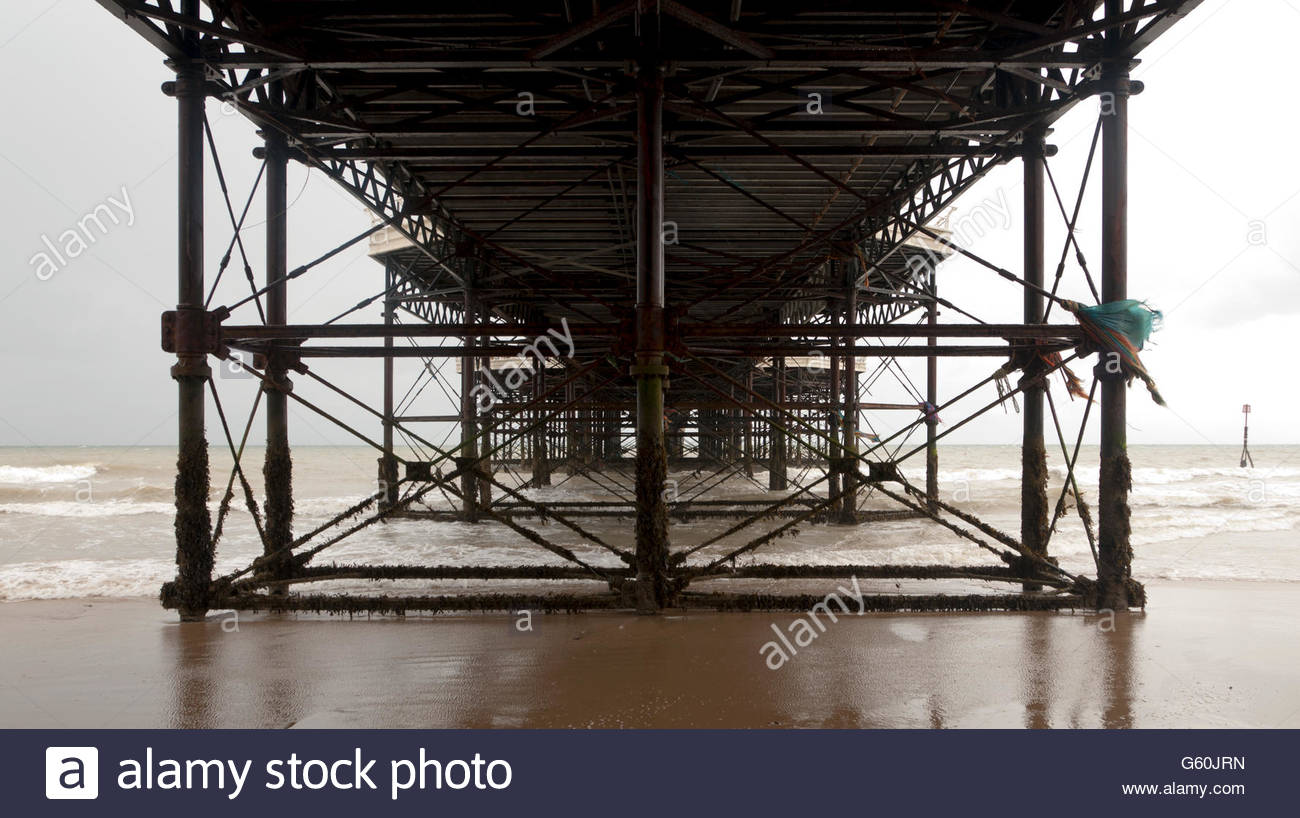 Pier substructure in rain on beach - Stock Image