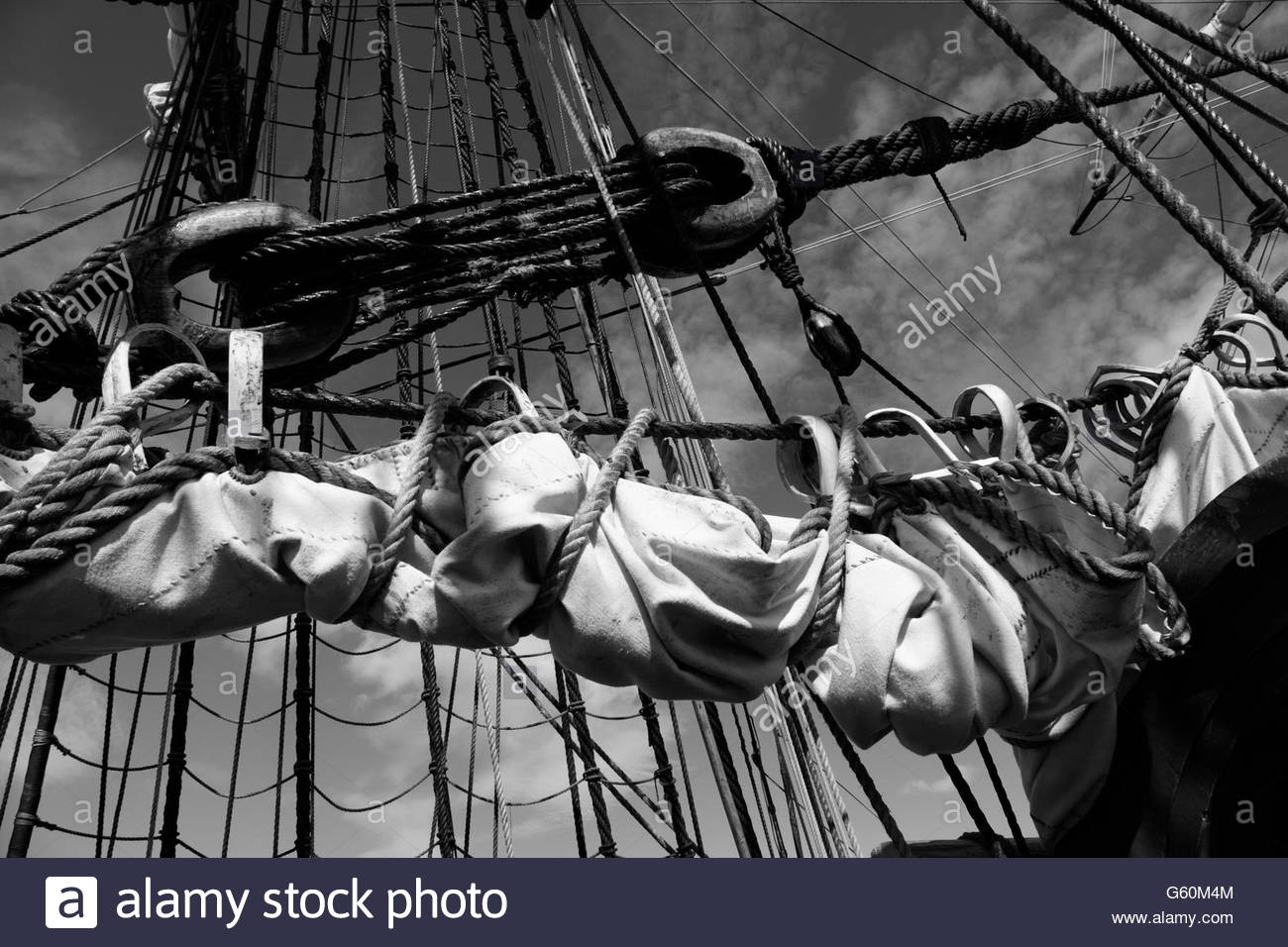 Reefed canvas sail and rigging of a tall ship - Stock Image