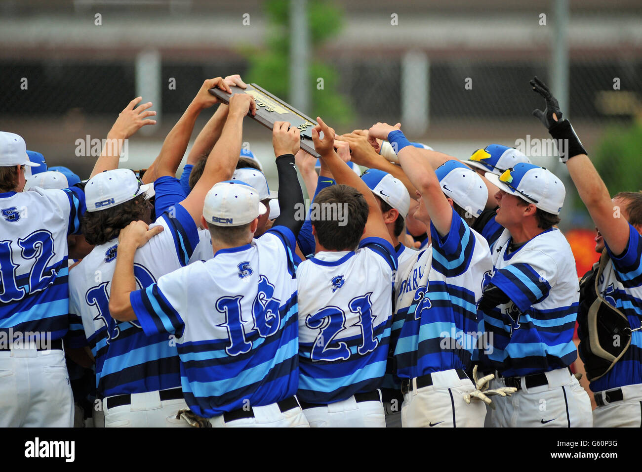 Players rally around a sectional championship plaque they has just won with an on-field victory. USA. - Stock Image
