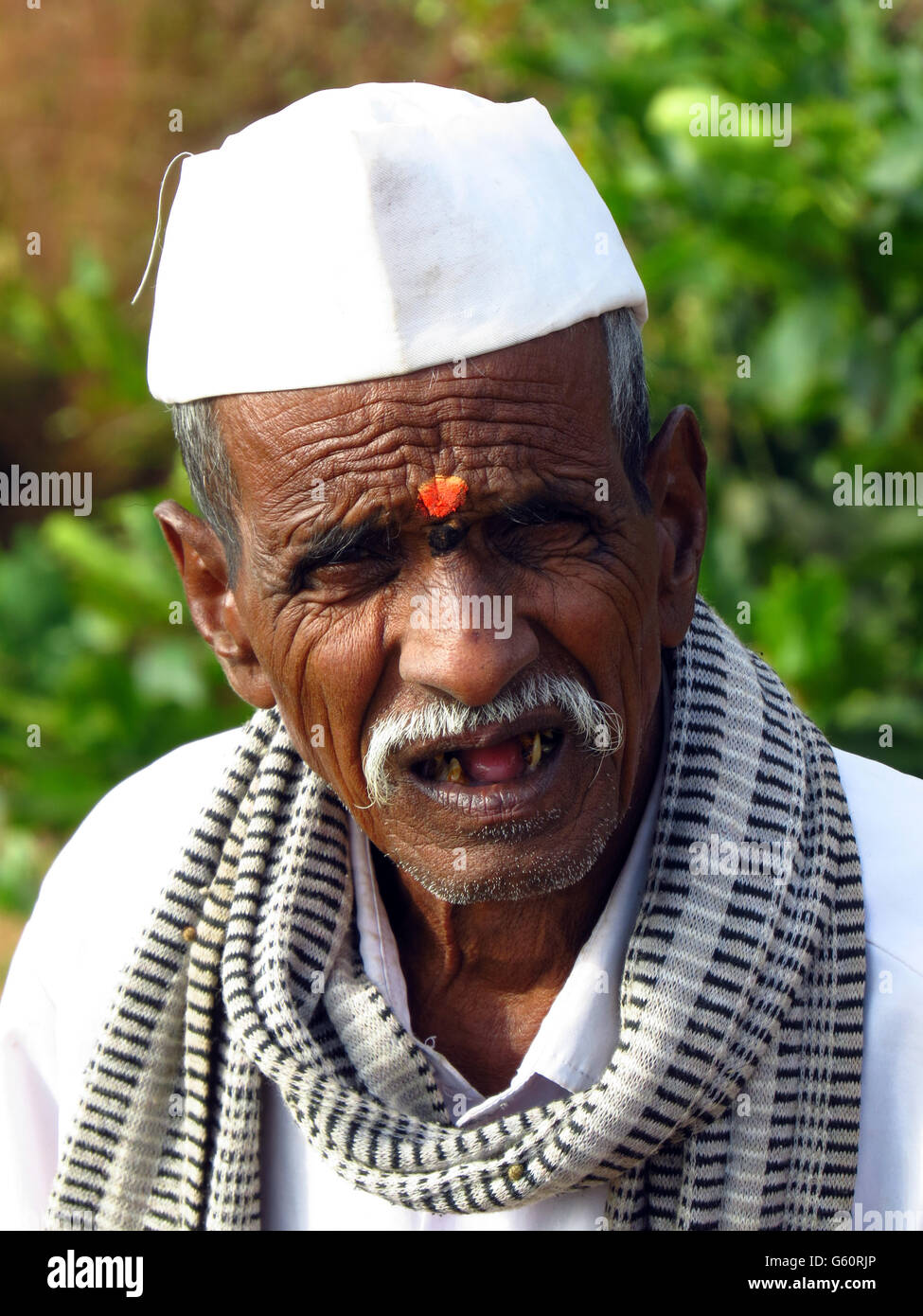 A poor old man from an Indian village with a wrinkled face aged with wisdom - Stock Image