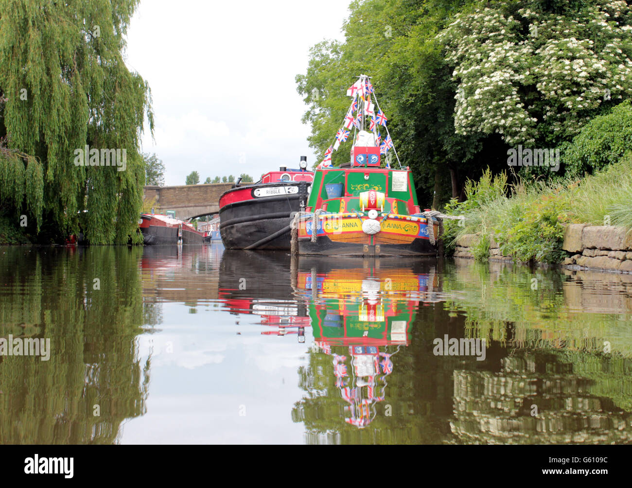 Boats on the Leeds and Liverpool canal in Burscough at the Wharf, West Lancashire, view from water level. - Stock Image