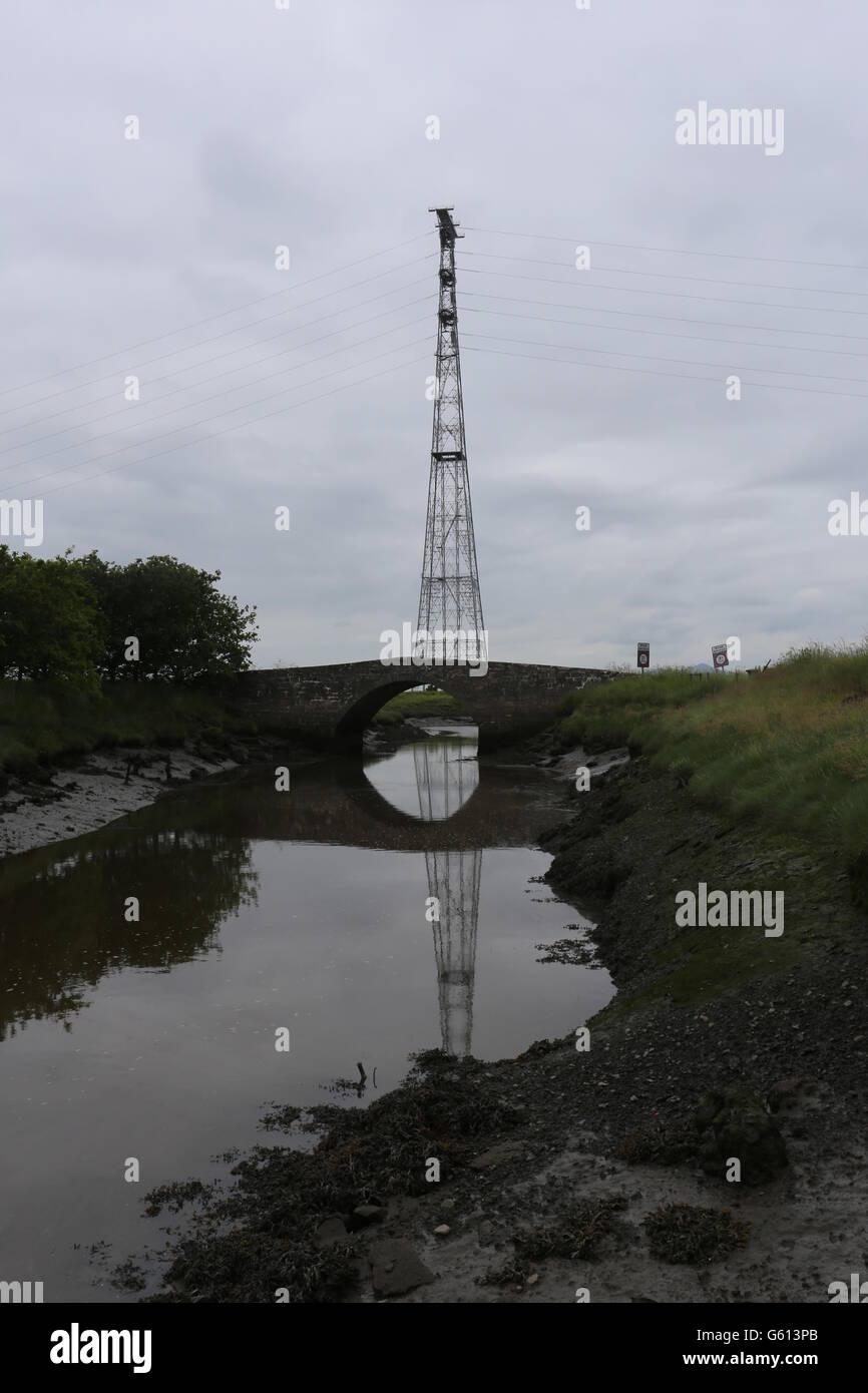 South Pylon of the 400kV Forth Crossing and humpbacked bridge over small stream Scotland  June 2016 - Stock Image