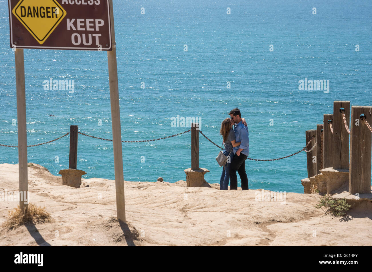Romantic couple with ironic warning sign - Stock Image