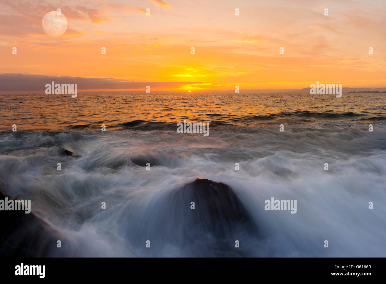 Ocean sunset is a brightly lit golden seascape with a gentle wave rolling to the shore. Stock Photo
