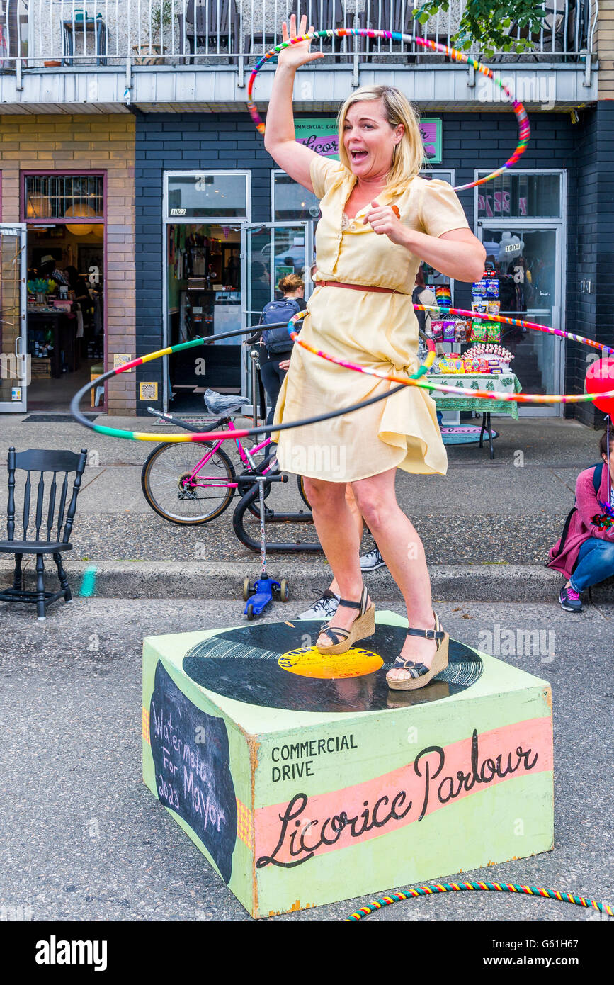 Mary Jean Dunsdon does Hula hoop demo outside her licorice parlour candy store, Italian Day, Commercial Drive, Vancouver, - Stock Image