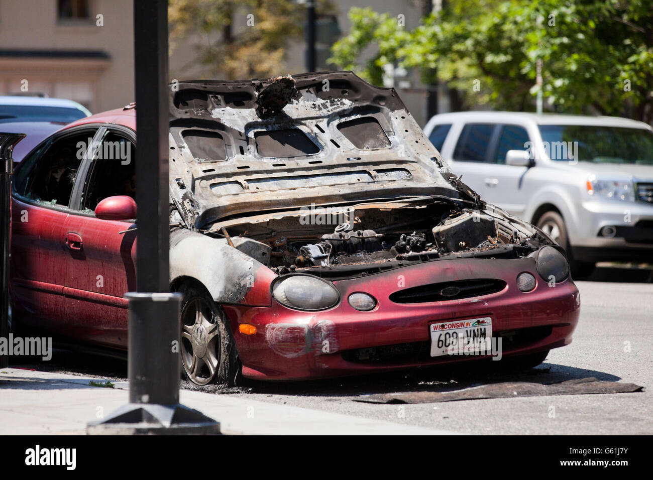Fire damaged car parked on road - USA - Stock Image