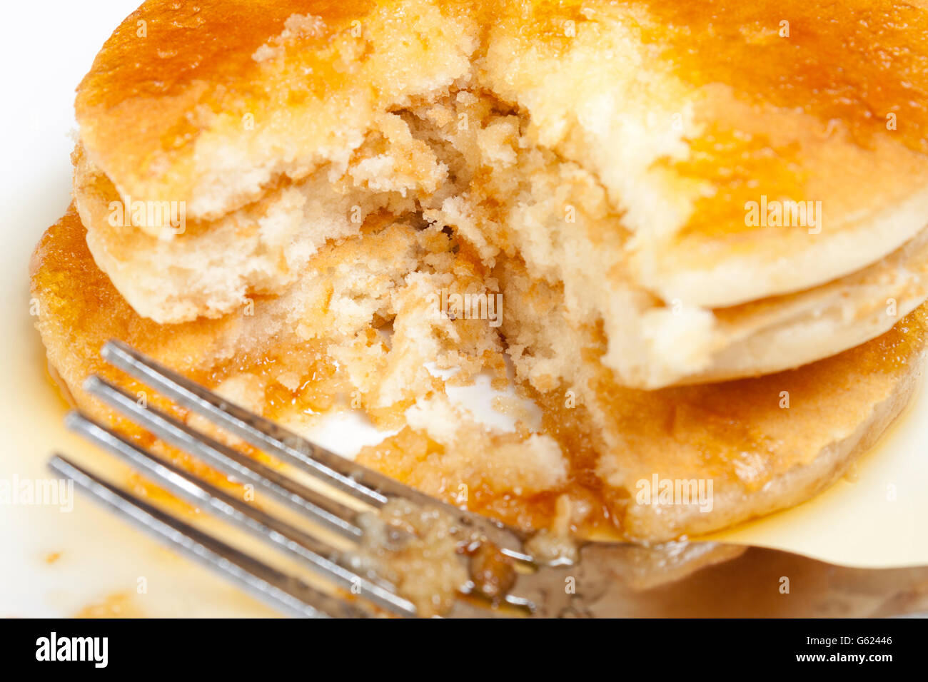 Close up shot of a stack of fresh golden pancakes covered in maple syrup with a fork viewed from above - Stock Image