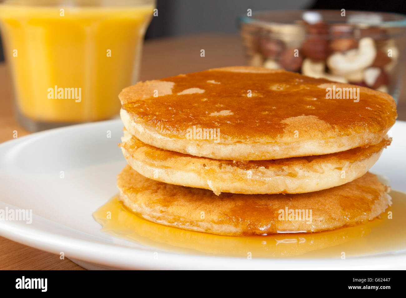 Close up shot of a stack of fresh golden pancakes on a plate covered in rich maple syrup aside a glass of fresh - Stock Image