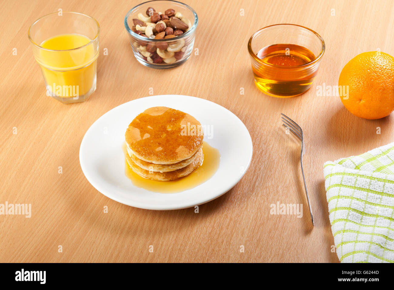 Plate of syrup covered pancakes with a bowl of mixed nuts and dried fruit on a breakfast table with a glass of fresh - Stock Image