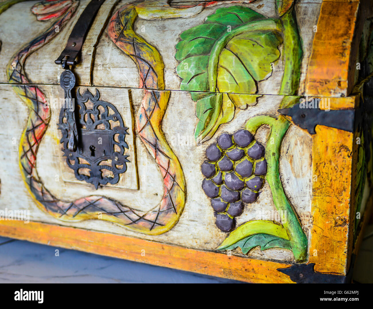A charming & whimsical folk art style wood carved trunk depicting snakes and grapes and birds with decorative metal Stock Photo