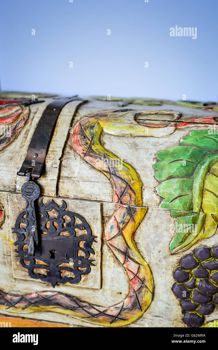 A charming & whimsical folk art style wood carved trunk depicting snakes and grapes and birds with decorative - Stock Image