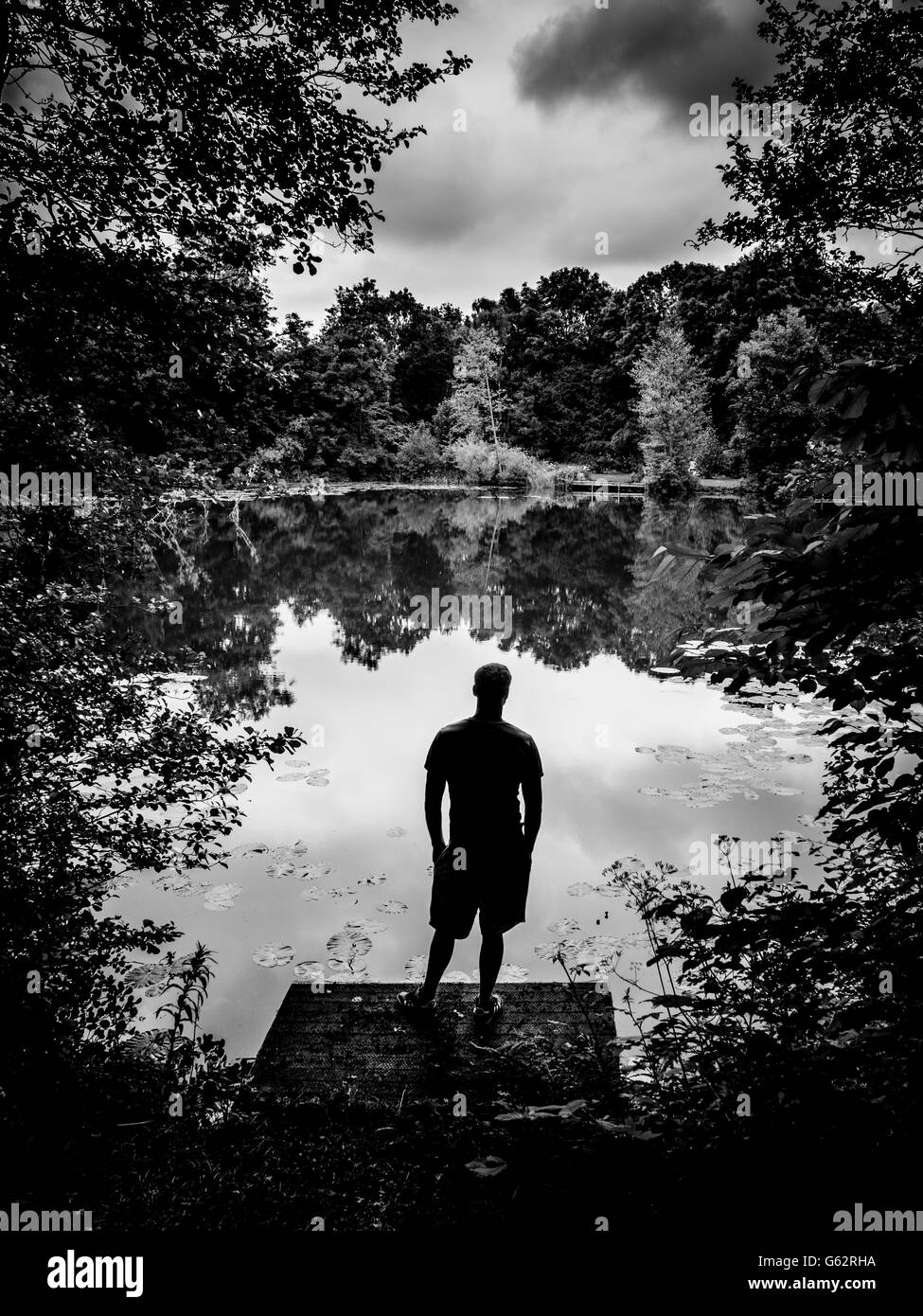 Silhouette of man stood on wooden jetty looking gout over lake with trees surrounding edges - Stock Image