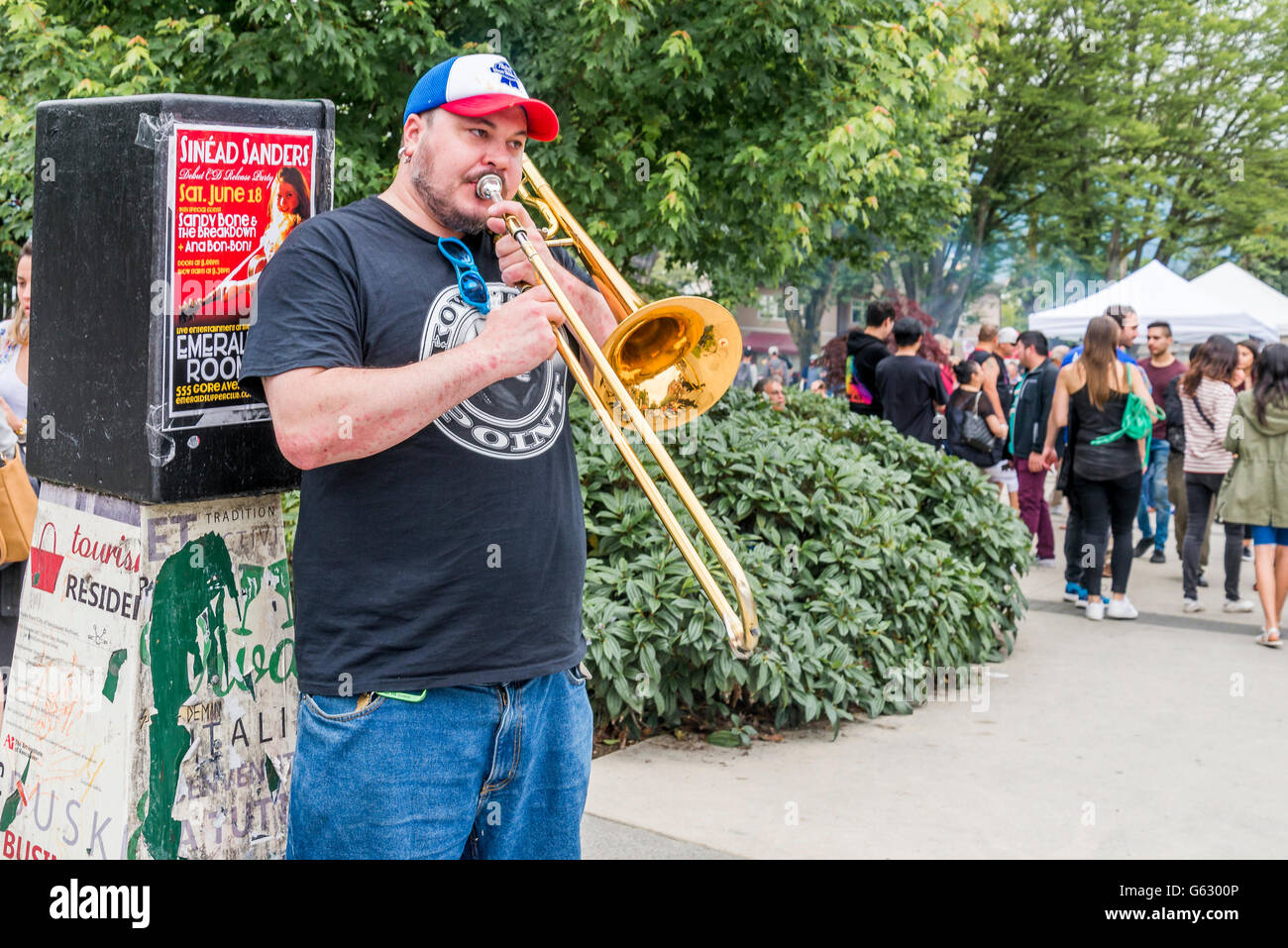 Busker playing trombone, Commercial Drive, Vancouver, British Columbia, Canada - Stock Image