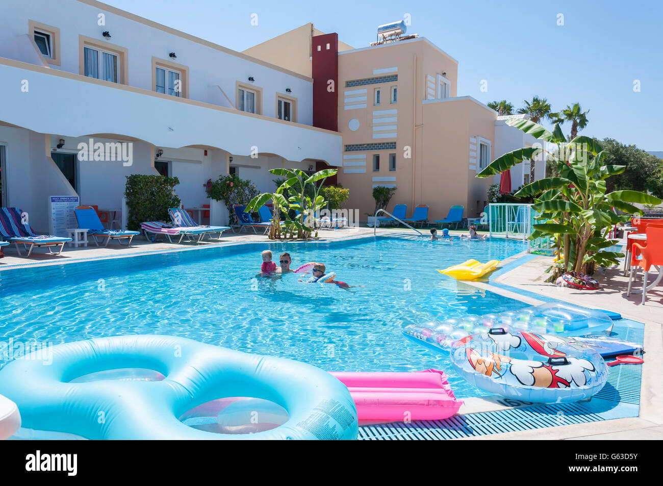 Family in swimming pool at Alice Springs Hotel, Lambi, Kos (Cos), The Dodecanese, South Aegean Region, Greece - Stock Image