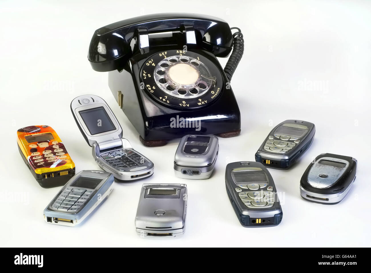 Old working cell phones and black rotary telephone. - Stock Image