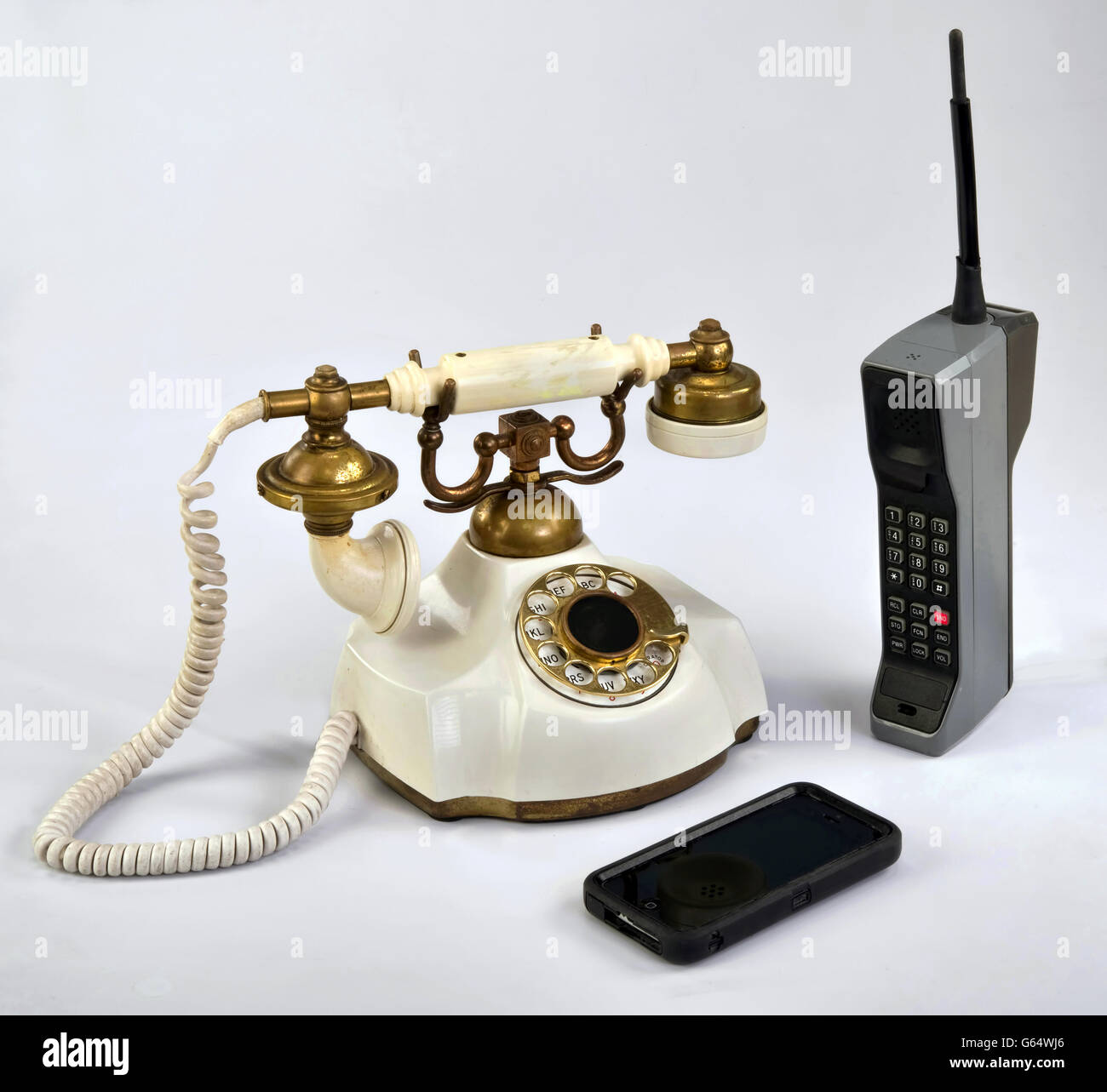 Working smart cell phone and old white rotary telephone. - Stock Image