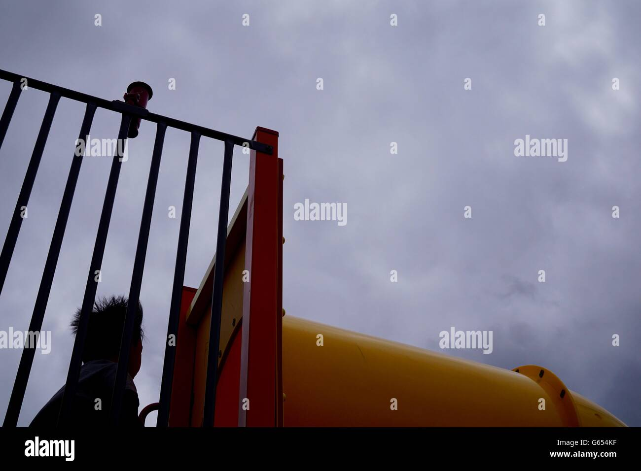 Boy looking up at overcast sky in the playground - Stock Image