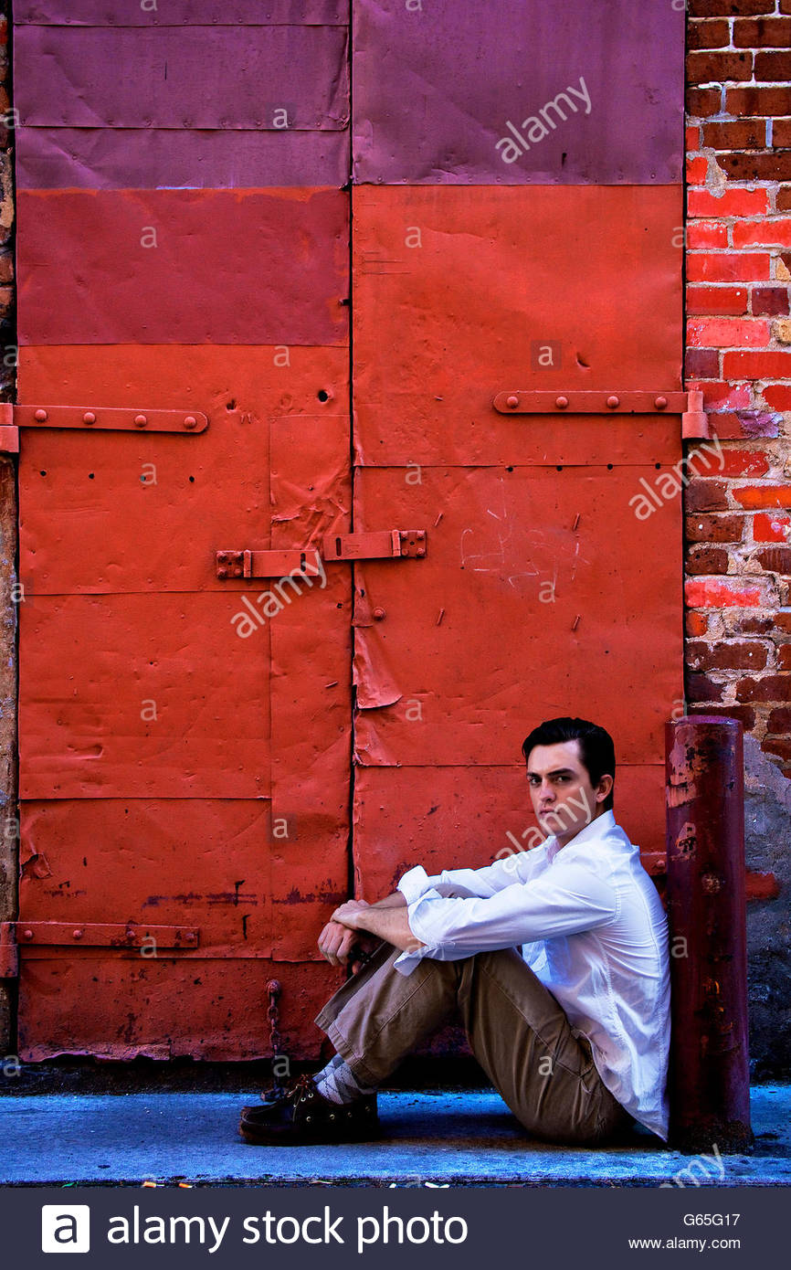 Young man sitting in alley, staring belligerently at the camera. - Stock Image
