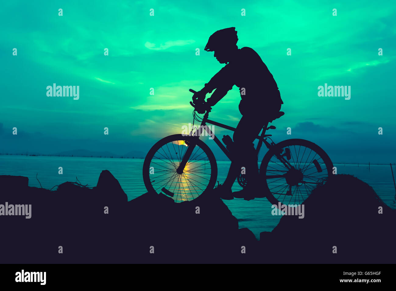 Silhouette of bicyclist riding the bike on a rocky trail at seaside, on colorful sunset sky background. Active outdoors - Stock Image